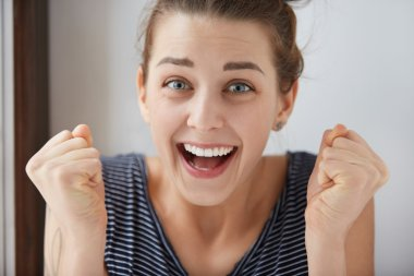Close-up shot of smiling blue-eyes European girl clenching her fists in endless joy. Positive emotions and feeling of deserved triumph makes charming woman look gorgeous on white background.