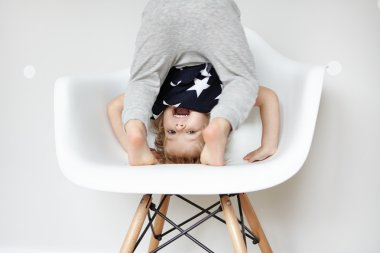 Indoor portrait of beautiful toddler dressed in stylish pajamas with stars, trying to do somersault on white chair in children's room. Caucasian preschool kid having fun and playing on his own at home