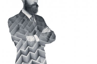 Cropped shot of confident and thoughtful businessman or officer worker wearing suit standing with arms folded on white blank wall. Double exposure of man's body silhouette with maze on it