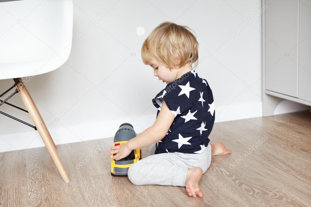 Houten Vloeren Haren : Schattige babyjongen met blonde haren zitten op houten vloer in