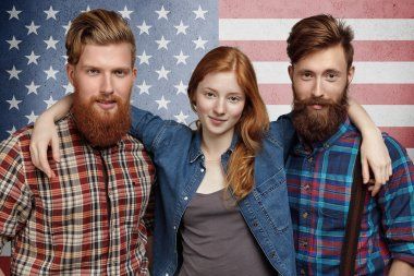 People, freedom, happiness and friendship concept. Group of happy American patriots dressed in stylish clothes, posing together against US flag background. Pretty girl hugging her two male friends