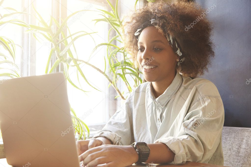 Young attractive dark-skinned female freelancer using laptop computer at cafeteria for distant work. Stylish student girl with nose-ring surfing Internet and messaging friends via social networks