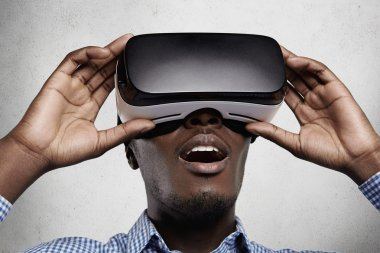 Close up of drak-skinned man in checkered t-shirt and 3d headset, watching something fascinating and surprising while experiencing virtual reality. Surprised African businessman using oculus glasses
