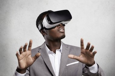 Gaming, 3d technology and cyberspace. Dark-skinned entrepreneur in formal suit experiencing virtual reality, playing video games using oculus rift headset, gesturing as if interacting with something