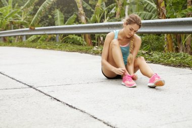 Female runner lacing pink running shoes