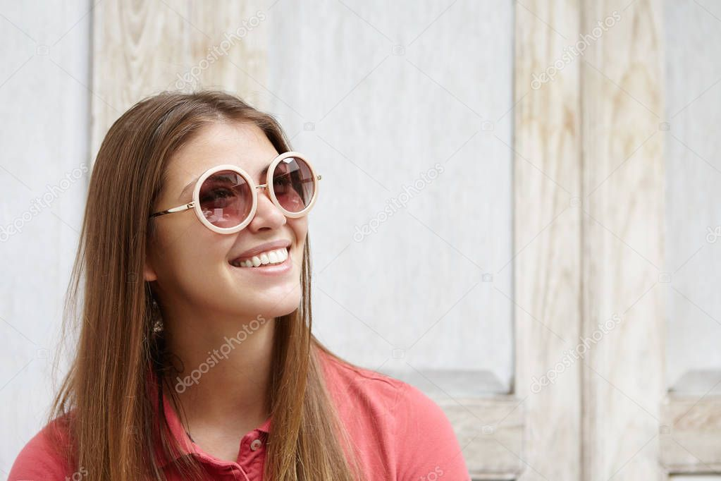 fashionable woman in round shades smiling