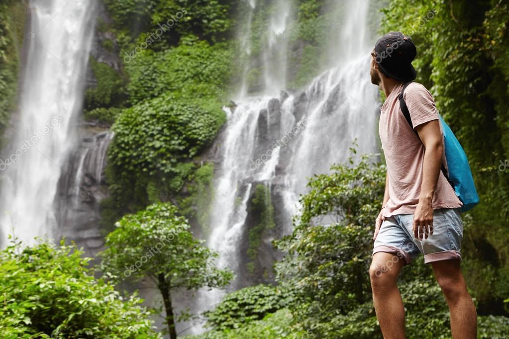 adventurer with backpack contemplating waterfall landscape