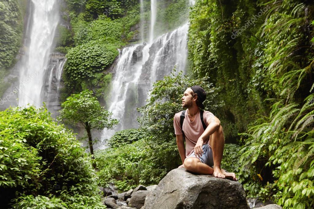 tourist sitting on big rock