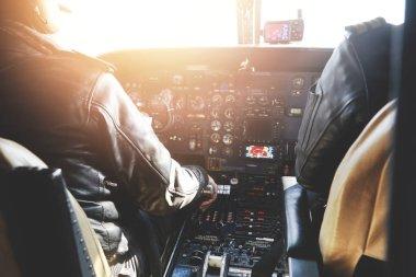 pilots dressed in uniform flying jet airliner
