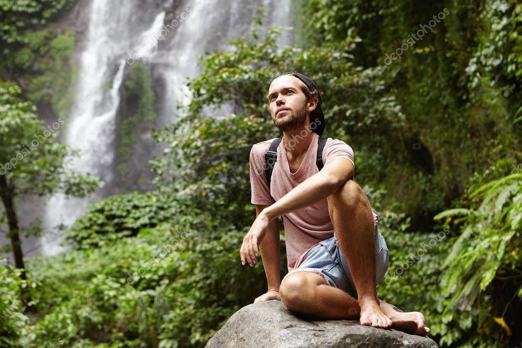 man sitting barefooted on big stone