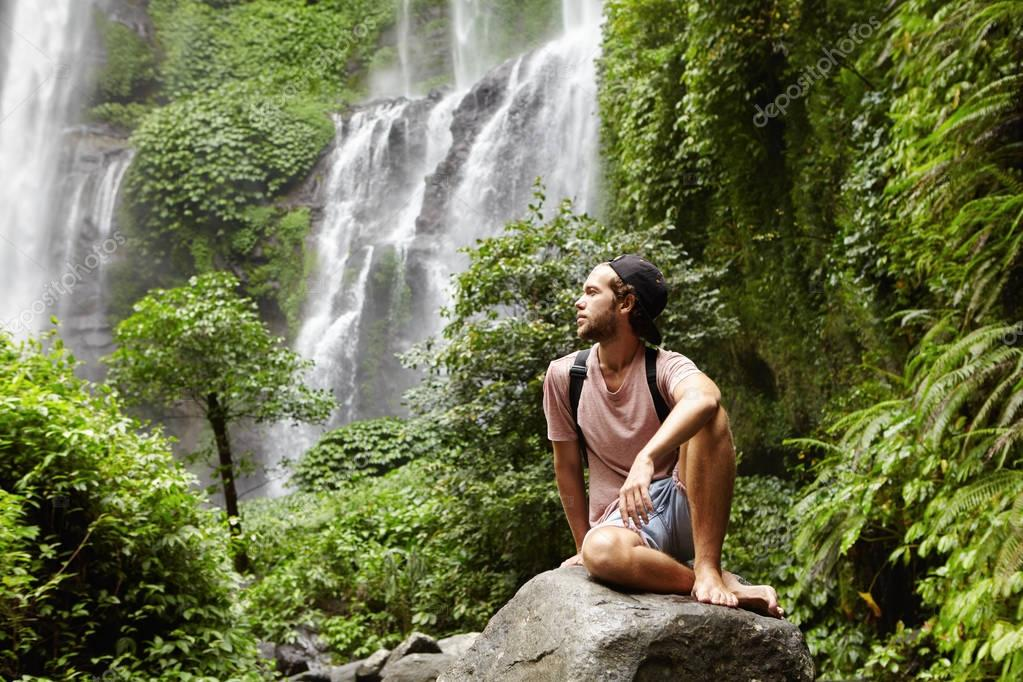 barefooted male  sitting on rock