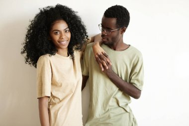 Happy to be together. Handsome young African male wearing glasses clasping hands together with his beautiful girlfriend with stylish Afro haircut and braces, celebrating Saint Valentine's Day at home