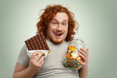 man holding chocolate and jar of candies