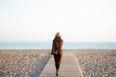 stylish woman walking along boardwalk