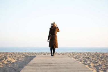 fashionable girl standing on boardwalk