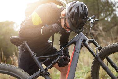 Rider repairing his booster bicycle