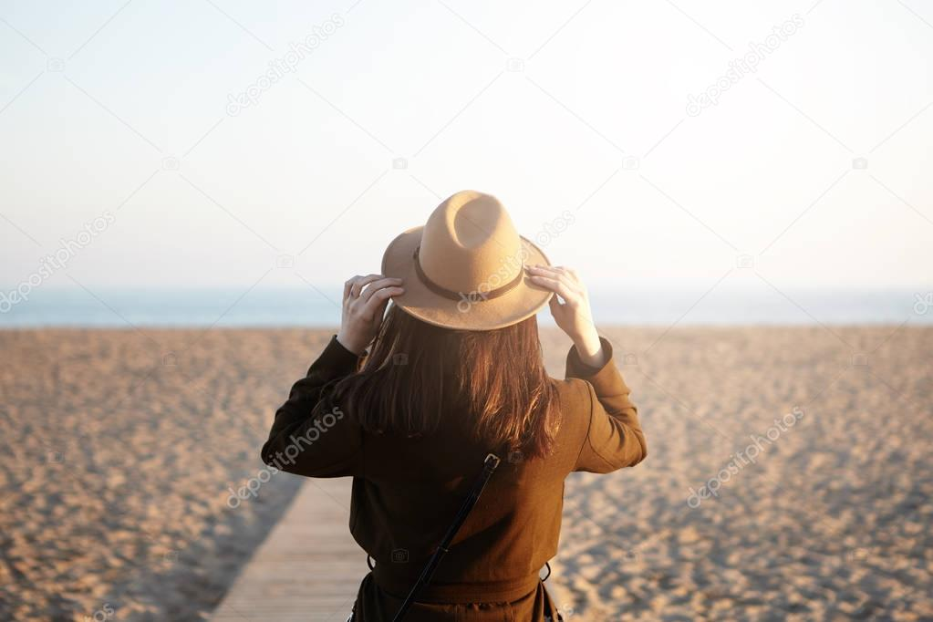 unrecognizable woman walking along boardwalk