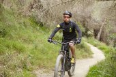 Photo professional rider with stubble riding electric bike