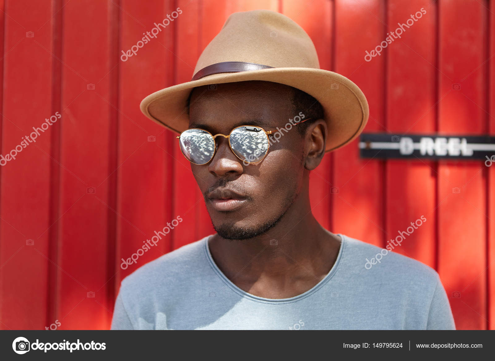 Portrait of stylish handsome young Afro-American man with bristle standing  outdoors against red wall background on sunny day wearing t-shirt da06c4000a39