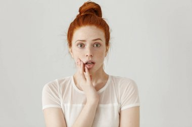 redhead freckled female raising eyebrows