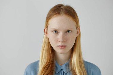 Portrait of gorgeous European teenage girl with freckles and blue eyes wearing her blonde loose hair tucked behind ears, standing isolated against grey studio wall background, looking seriously