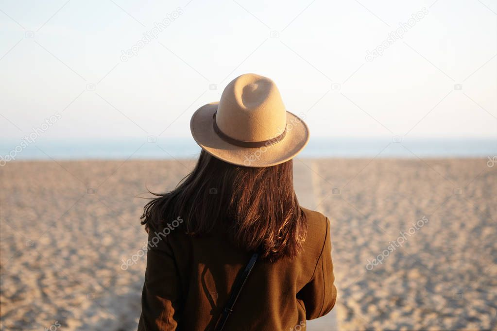 woman in hat and coat going towards sea