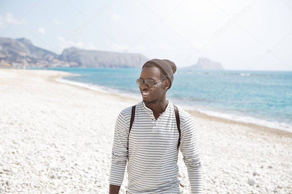 Afro American traveler walk along seashore