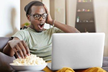 dark-skinned man watching football