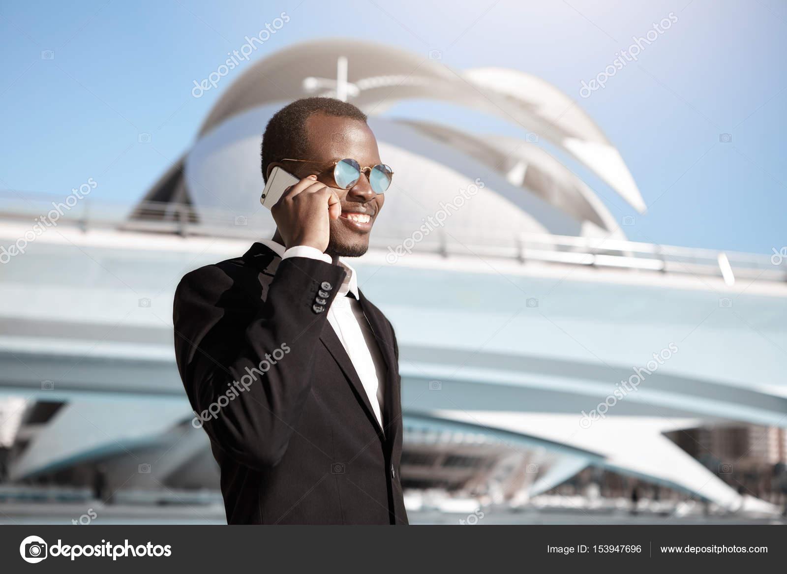 7ecd1bf832 Piel oscura hombre de negocios acertado con elegante traje negro y gafas de  sol redondas haber complacido sonrisa mientras habla sobre smartphone con  su ...