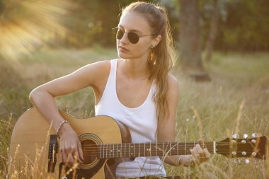 Female playing guitar while sitting alone