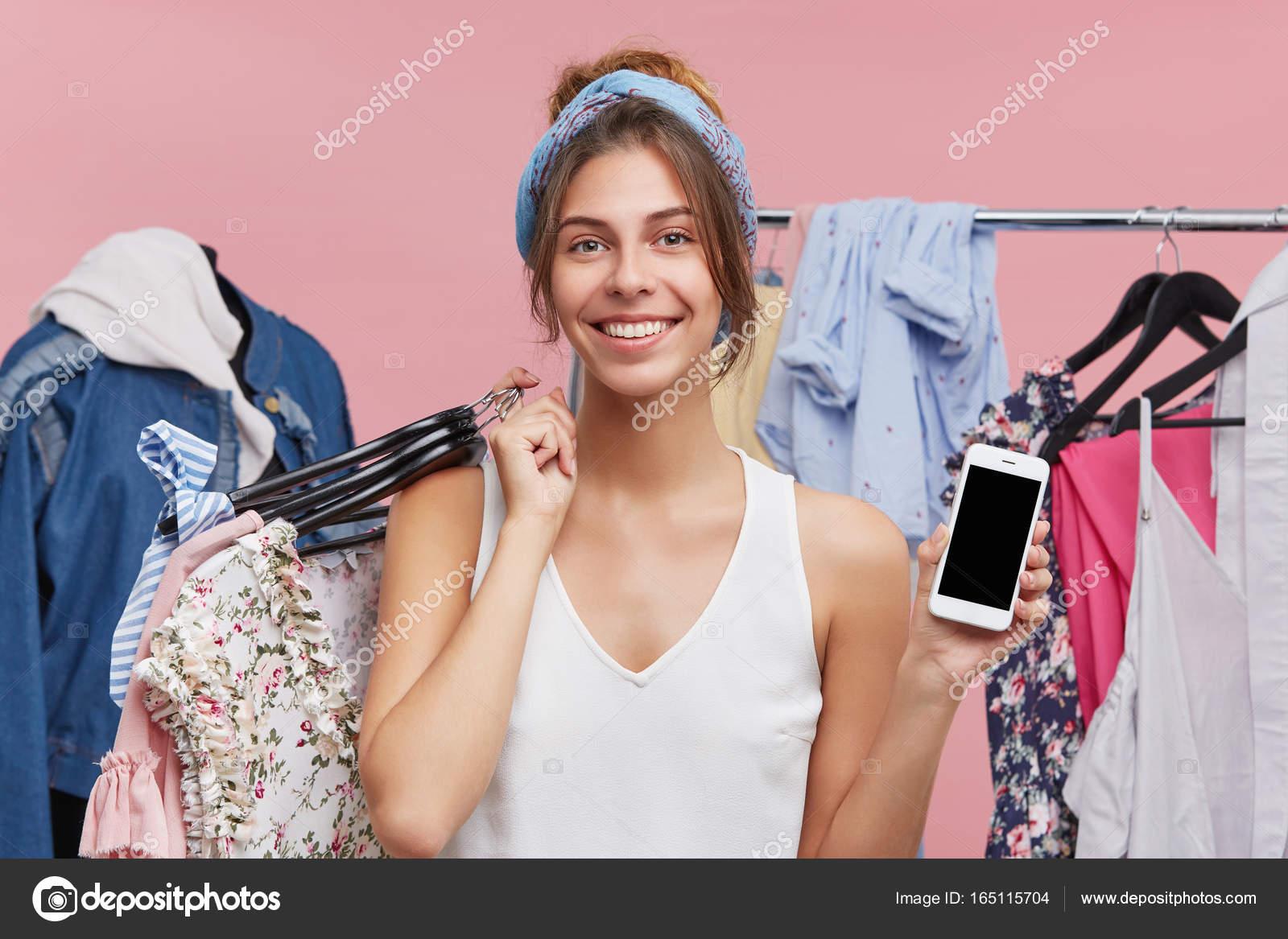 Розничная торговля, продажа, потребительства и концепции современной  технологии. Портрет очаровательный молодой женщины стоя на стойку с модной  одежды, ... 0e44c741261