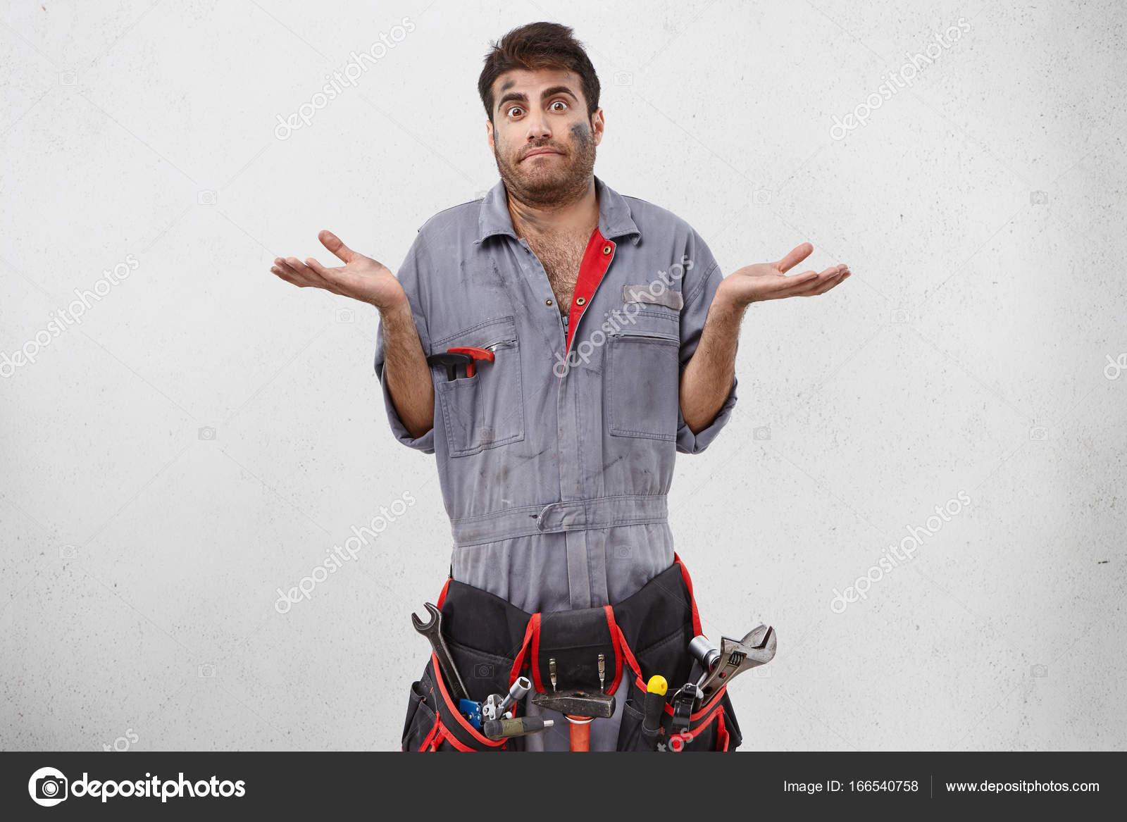 83fd3a2c760e Coup de Studio d émotionnel désemparé jeune mal rasé mâle plombier avec kit  de ceinture d outils de travail avoir confondu le regard perplexe, haussant  les ...