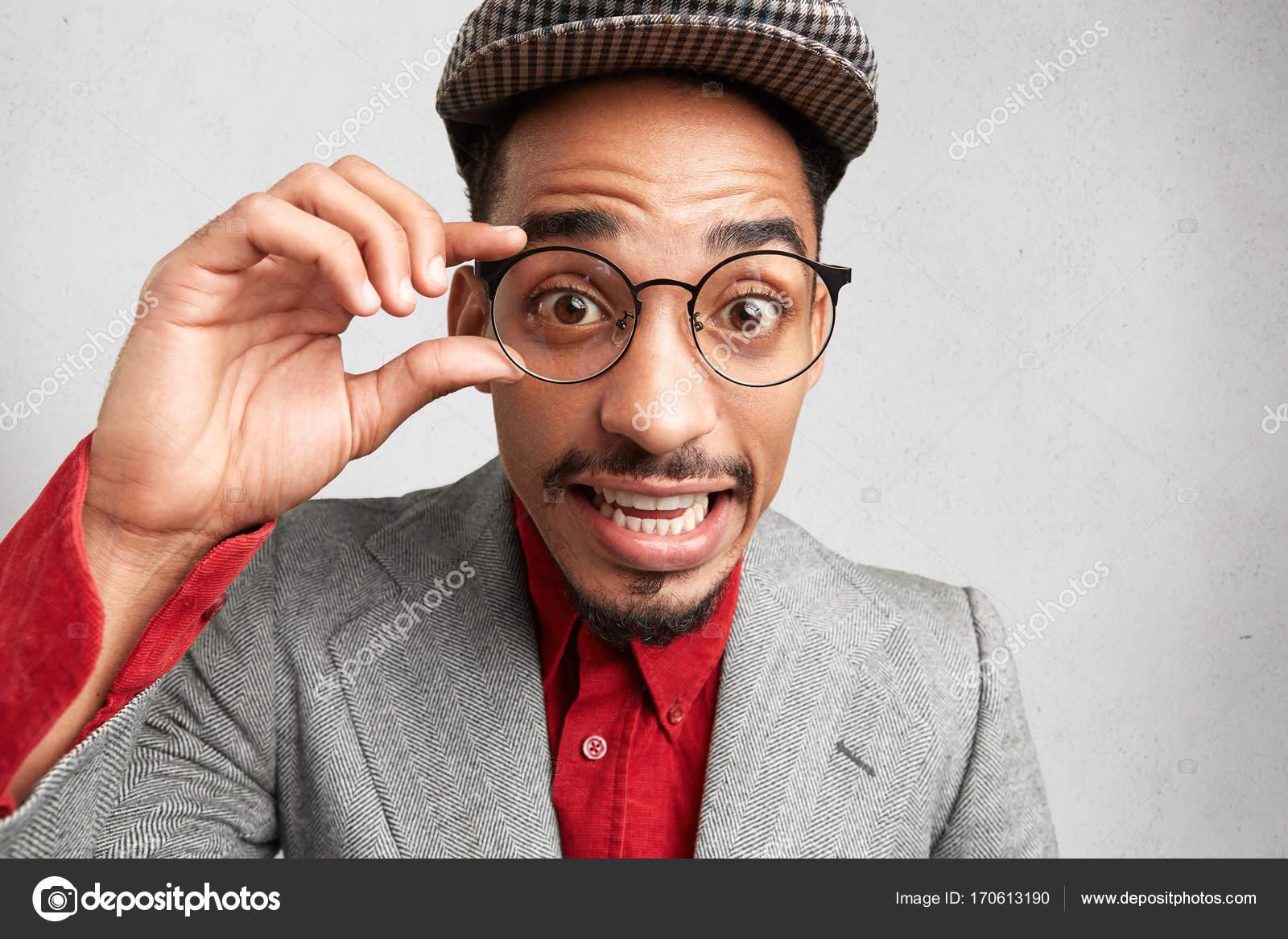 Sorprendido varón nerd usa gafas redondas, mantiene la mano en el ...