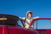 Fotografie 40s woman hippy style enjoy the weather outside of her old red car. Vintage life and style, blue clear sky background