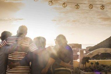 Grup 4 kişi kıdemli erotik yaşlı sarılmak ve çatıdaki batımını güneş aydınlatmalı ve altın renkleri ile beraber. harika manzaralı teras ile tatil kavramı evde. dostluk eğlence açık hava etkinliği