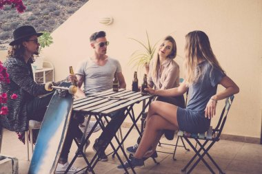 group of 4 young women and men drinking beer on the rooftop terrace in vacation. Happy time and relax concept. warm and vintage filter. Old wood table and long board for trendy people.