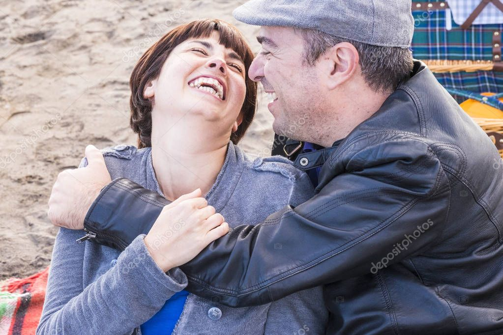 cute man and woman middle aged having fun in love at the beach outdoor. leisure activity and big smile and laugh for the lady. the man embrace her. picnic cest on the background