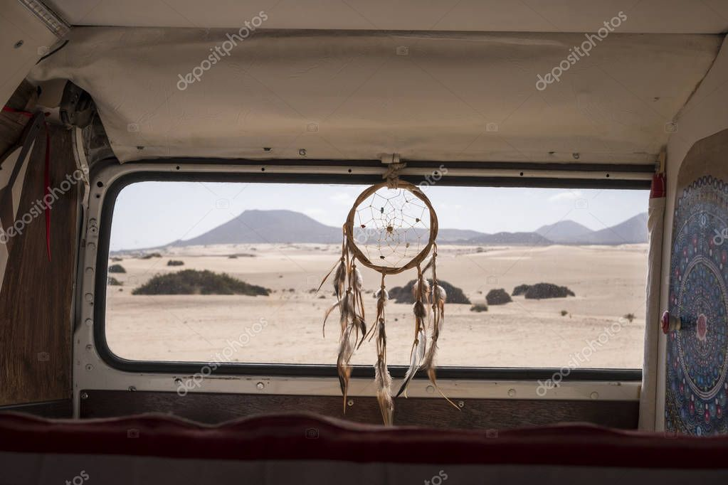 vanlife concept for different alternative life and wy of travel. Dreamcatcher on the window with desert and mountains outdoor. mandale at the left, quiet situation