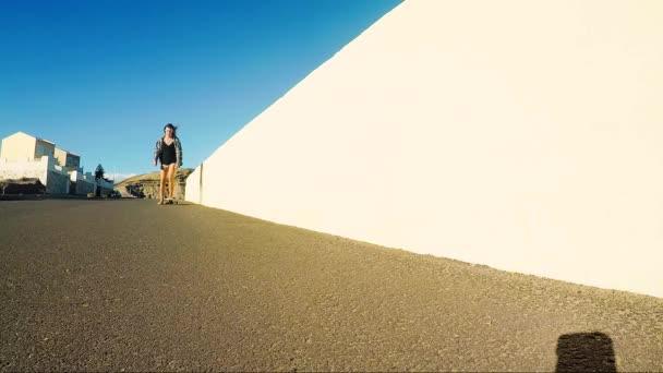 krásné alternativní rebel mladá žena na skateboard na silnici kopci v tenerife během slunečného dne. hory v pozadí.