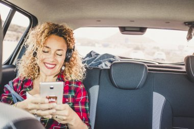 Cheerful happy woman sit down on the back seats inside a modern car using a cellular phone to listen music with headphones
