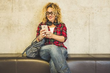Beautiful happy caucasian woman sit down on a sofa and use mobile phone