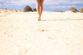Photo Close up of nude young beautiful woman legs walking on the soft sand at the beach in summer holiday free vacation