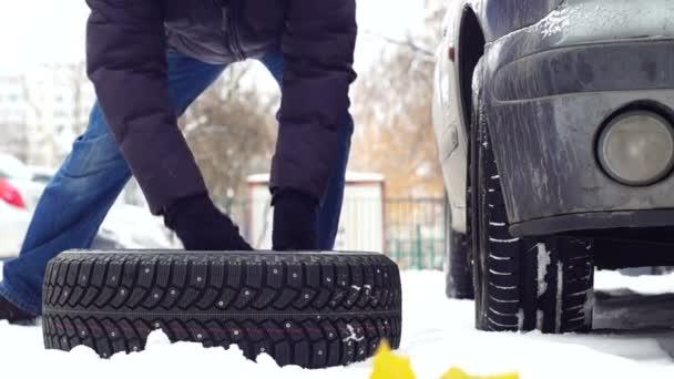 Muž Stohovací sada nové zimní pneumatiky poblíž staré auto