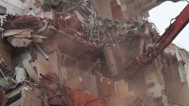 Rypadlo ničí dům pomocí hydraulických nůžek