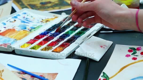 Hände von Jugendlichen zeichnen Aquarelle