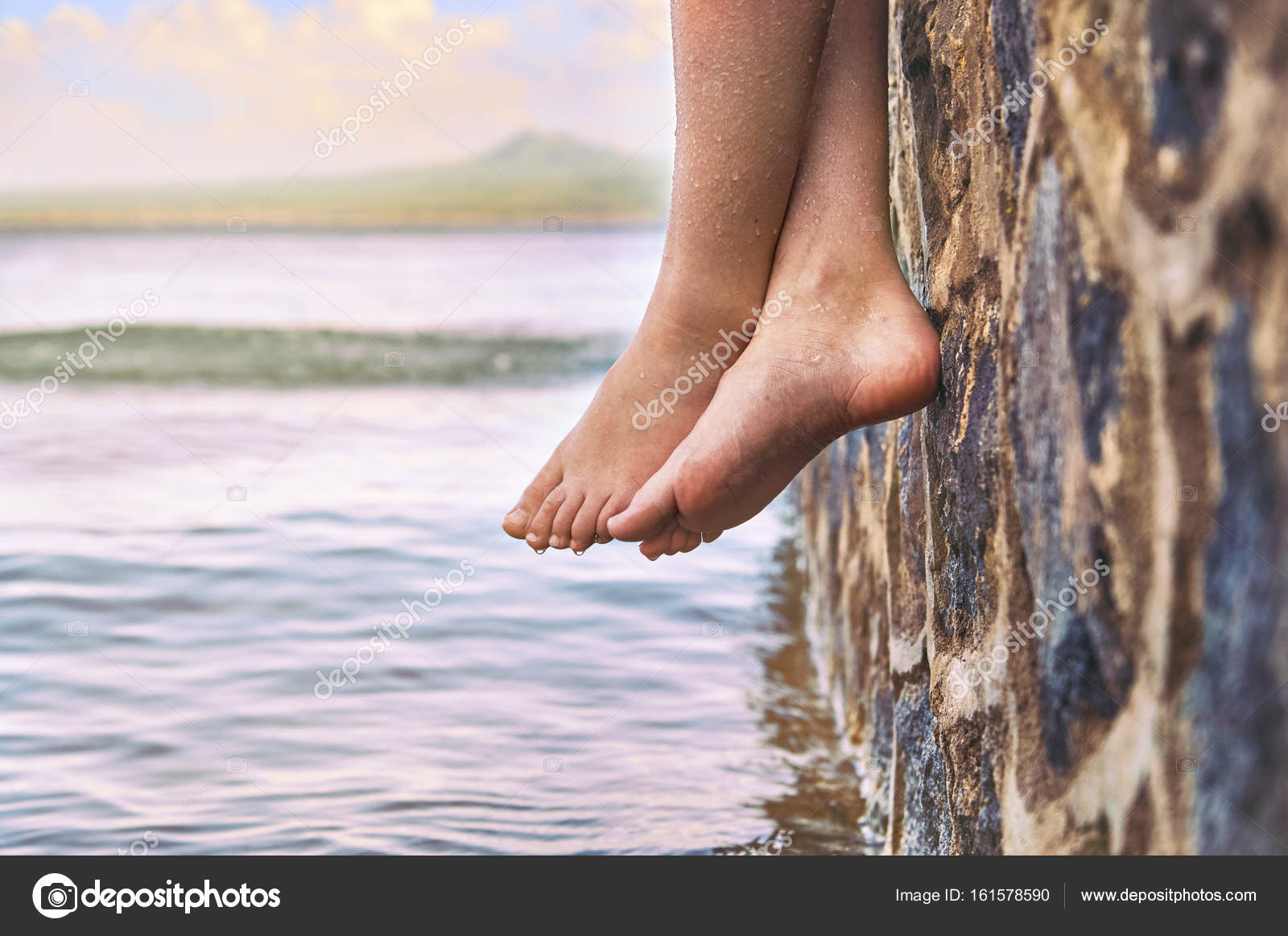 young girls feet dangling from the stone jetty stock photo