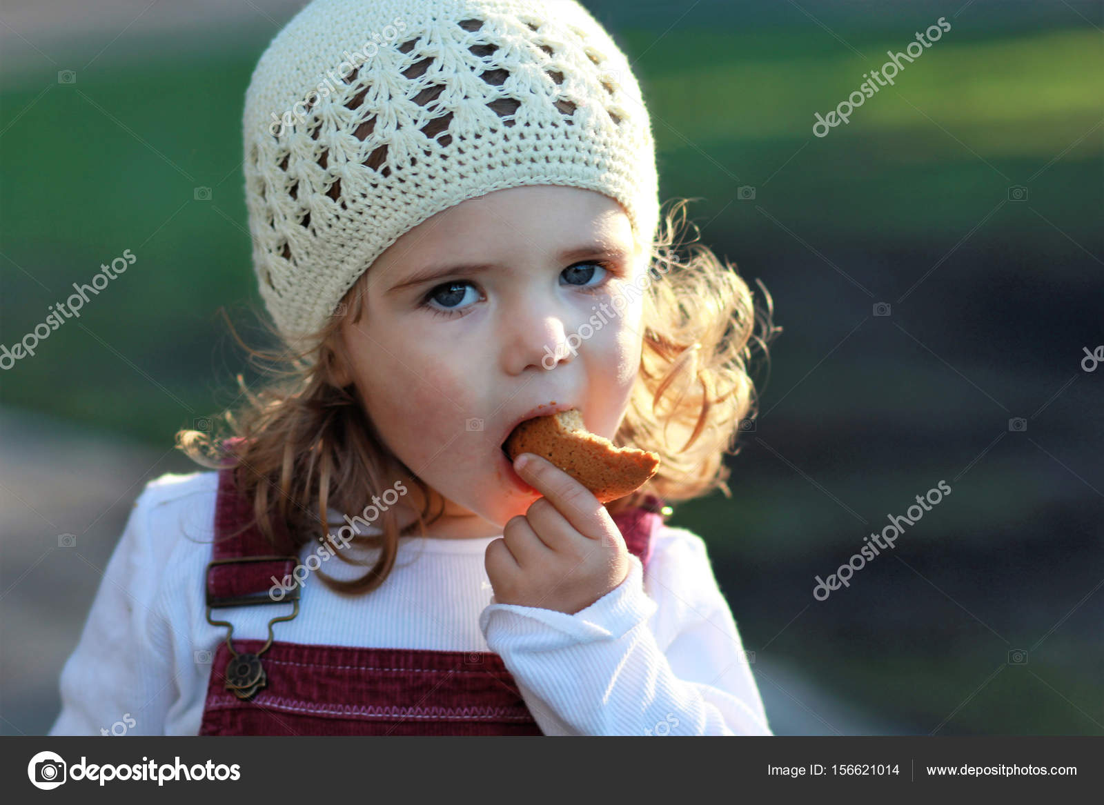 9cb62ef12e5 Close up portrait of cute one year old girl in a white knitted hat eating  cookie on a stroll in the park