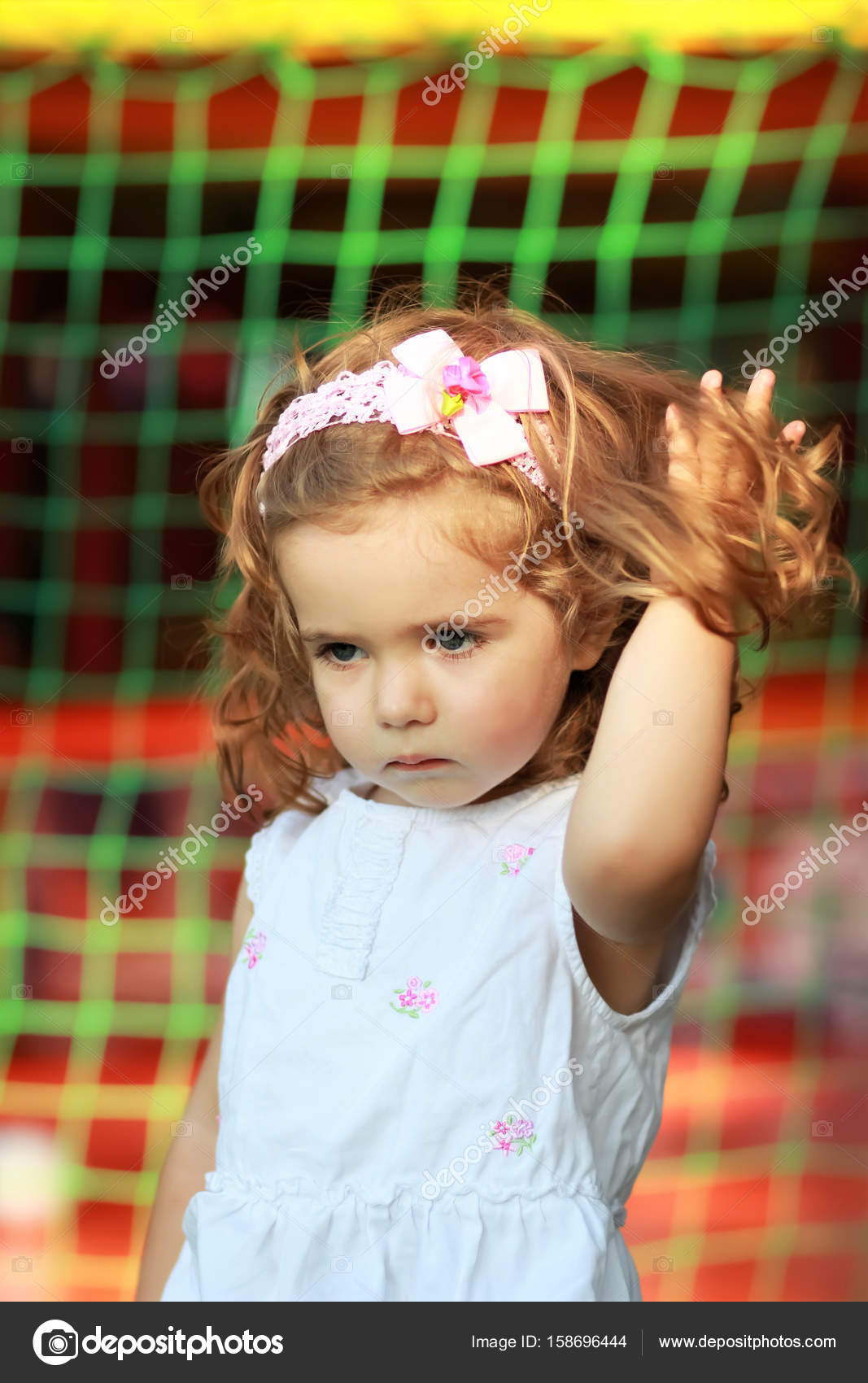 Portrait of a sweet one year old girl with pink head band with bow and  flower in the summer park, hand stuck in long curly hair — Photo by Mr_Ptica
