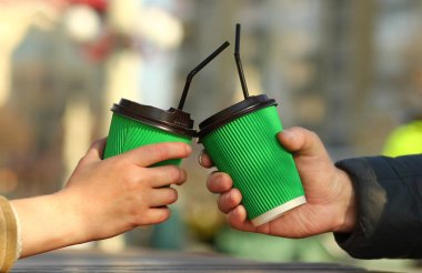 Man's and woman's hands closeup holding green paper coffee cups, place for logo