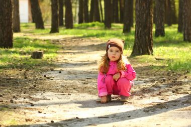 Cheerful toddler girl posing in the sunlit spring forest